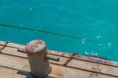 Oude, roestige meerpaal met metaalketting op pijler met water Stock Foto