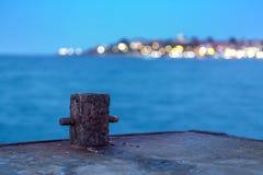 Oude roestige meerpaal op het dok bij nacht stock fotografie