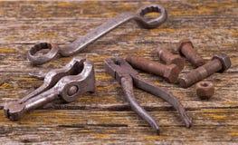 Oude roestige noten, bouten Oude hulpmiddelen raad stock foto's