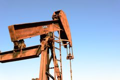 Oude roestige olieboortoren in zonlicht met blauwe hemel Stock Foto's