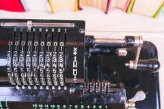 Oude roestige retro calculator zwarte status op een houten lijst Stock Afbeelding