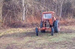 Oude roestige rode antieke tractor van een landbouwbedrijf in het hout stock afbeelding