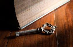 Oude roestige sleutel met een deel van antiek boek Royalty-vrije Stock Afbeeldingen