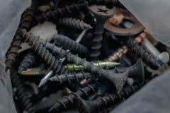 Oude roestige spijkers en schroeven als achtergrond en textuur stock afbeelding