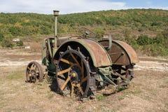 Oude roestige tractor op een gebied Stock Foto's