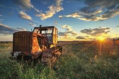 Oude roestige tractor op een gebied op zonsondergang Royalty-vrije Stock Foto's