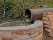 Oude roestige uitstekende drainagepijp die in een waterbassin leegmaken in het Park van het Geheugenbosje in Salt Lake City Utah  royalty-vrije stock fotografie