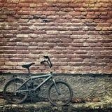 Oude roestige uitstekende fiets die tegen een bakstenen muur leunen Royalty-vrije Stock Foto