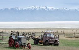 Oude roestige verlaten tractor en vrachtwagen op frot van snow-capped Wasatch-bergen Mening van Antilopeeiland Utah, de V royalty-vrije stock afbeelding