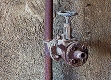 Oude roestige waterkraan in concrete muur Stock Afbeeldingen