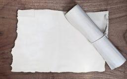 Oude rol met document op houten lijst royalty-vrije stock afbeeldingen