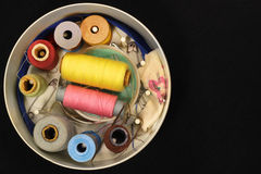 Oude ronde doos met spoelen van draad, naalden en spelden op zwarte achtergrond Royalty-vrije Stock Afbeeldingen
