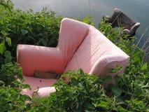 Oude roze leunstoel die in groen onkruid wordt gedumpt Stock Afbeeldingen
