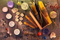 Oude runen, kaarsen, kristallen, kruiden en magische rituele voorwerpen op planken stock foto's