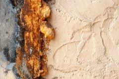 Oude ruwe beige geschilderde die muur met barsten en gat, met roestig nevelschuim worden behandeld stock foto's