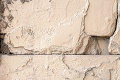 Oude ruwe beige geschilderde muur met barsten en gaten stock fotografie