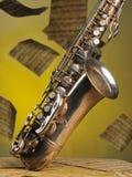 Oude saxofoon en vliegende muzieknoten op een backgr Stock Afbeeldingen