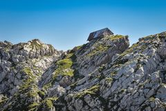 Oude schapenschuur op kalksteenrotsen in Julian Alps, Slovenië stock afbeeldingen