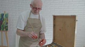 Oude schilders` s hand die verf met een borstel nemen, die zich dichtbij palet bevinden stock videobeelden