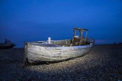 Oude schipbreuk in de zonsondergang op een pebbelstrand Royalty-vrije Stock Fotografie
