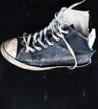 Oude schoen op zwarte raad Stock Afbeeldingen