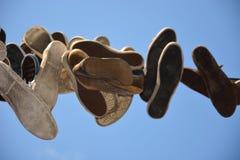 Oude schoenen die op een draad hangen Royalty-vrije Stock Foto's
