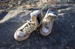 Oude schoenen op een rots stock afbeeldingen