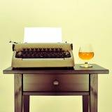 Oude schrijfmachine en alcoholische drank stock fotografie