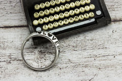 Oude schrijfmachine en ring met de inschrijvingsliefde Stock Fotografie