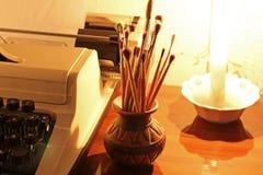 Oude schrijfmachine en verfborstels stock afbeeldingen