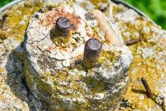 Oude schroeven in steen stock fotografie