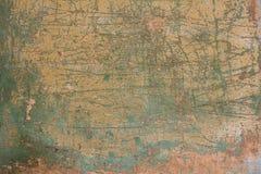 Oude sjofele roze gele concrete muur met barsten, diepe krassen en vlekken van groene verf en vuil Ruwe Oppervlaktetextuur royalty-vrije stock foto