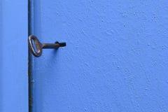 Oude sleutel in het sleutelgat Blauw, metaaldeur met een geweven oppervlakte stock afbeelding