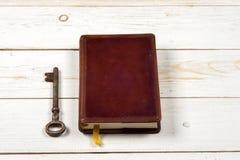 Oude sleutels op boek, antieke houten achtergrond Stock Foto