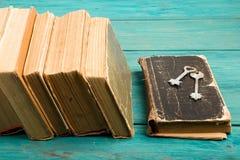 Oude sleutels op een oude boek en een stapel antieke boeken op blauwe houten Stock Fotografie