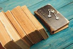 Oude sleutels op een oude boek en een stapel antieke boeken op blauwe houten Stock Afbeelding