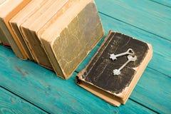 Oude sleutels op een oude boek en een stapel antieke boeken op blauwe houten Royalty-vrije Stock Afbeelding