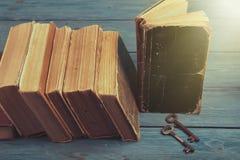 Oude sleutels op een oude boek en een stapel antieke boeken op blauwe houten Royalty-vrije Stock Fotografie