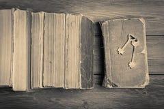 Oude sleutels op een oude boek en een stapel antieke boeken op houten rug Stock Afbeelding