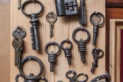Oude sleutels op houten muur Stock Afbeeldingen