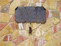 Oude sleutels op steenmuur, leeg uithangbord voor tekst Stock Afbeelding
