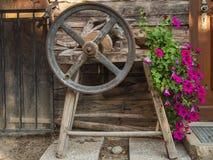 Oude slijpsteen met krukas en bloemen royalty-vrije stock afbeeldingen