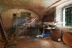 Oude, slordige kelderverdieping in oud huis Stock Foto