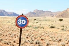 Oude snelheidsverkeersteken in woestijn en berglandschap Royalty-vrije Stock Foto's