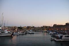 Oude Stad van Rhodos terwijl de roze zonsondergang, het kalme overzees, het Griekse monument en de haven bekijken Warme kleuren,  Stock Foto's