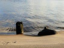 Oude stapels en steen op zandig rivierstrand Stock Fotografie