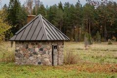 Oude steen die met nieuw dak bij een landbouwbedrijf op een rainny dag op het plattelandsgebied van Letland wordt afgeworpen royalty-vrije stock fotografie