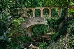 Oude steenbrug over de stroom royalty-vrije stock afbeeldingen