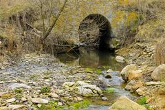 Oude steenbrug over kleine stroom Stock Afbeeldingen