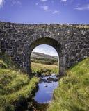 Oude steenbrug over stroom op Eiland van Skye stock afbeelding